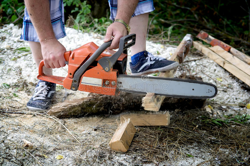 Chainsaw cutting firewood royalty free stock photo