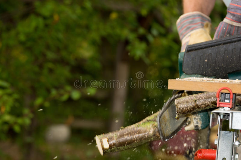 Chainsaw. A chainsaw cutting wood in the garden stock photography