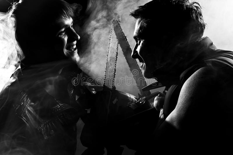 Chainsaw fight. Between two men and abstract smoke royalty free stock photography
