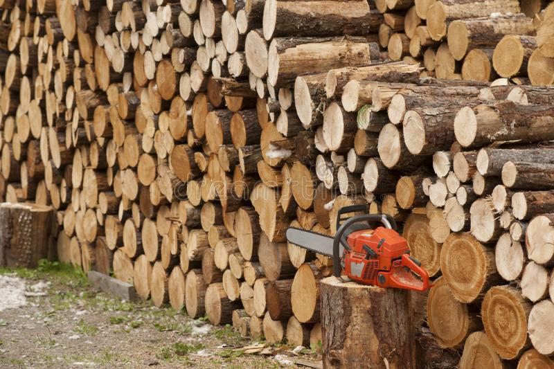 Chainsaw & Firewood Stack. A nice Stack of firewood together with a chainsaw in front stock photo