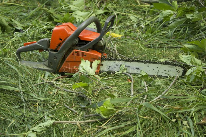 Chainsaw on a ground in the garden. Background royalty free stock images