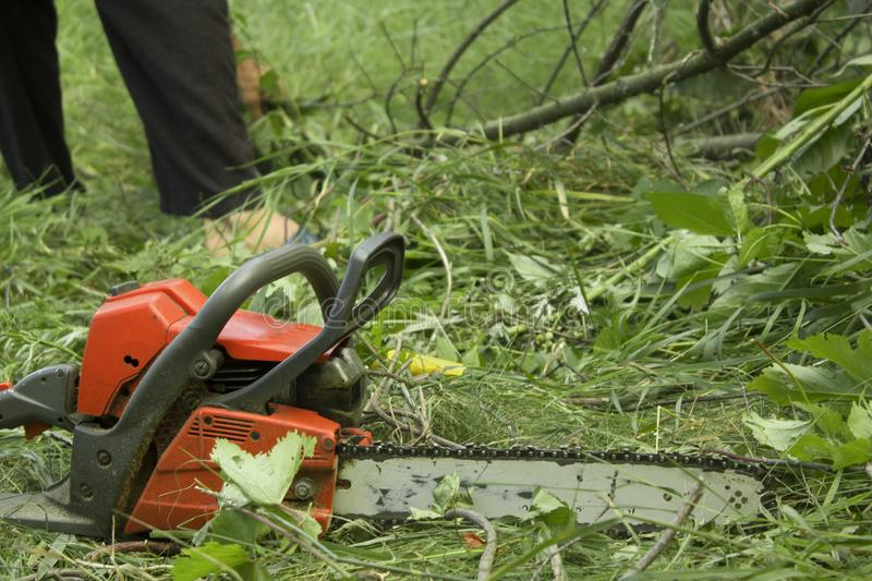 Chainsaw on a ground in the garden. Background royalty free stock photos