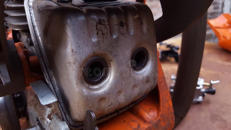 Chainsaw machine parts that are being serviced. Regular maintenance keeps the engine`s performance male and reliable royalty free stock image
