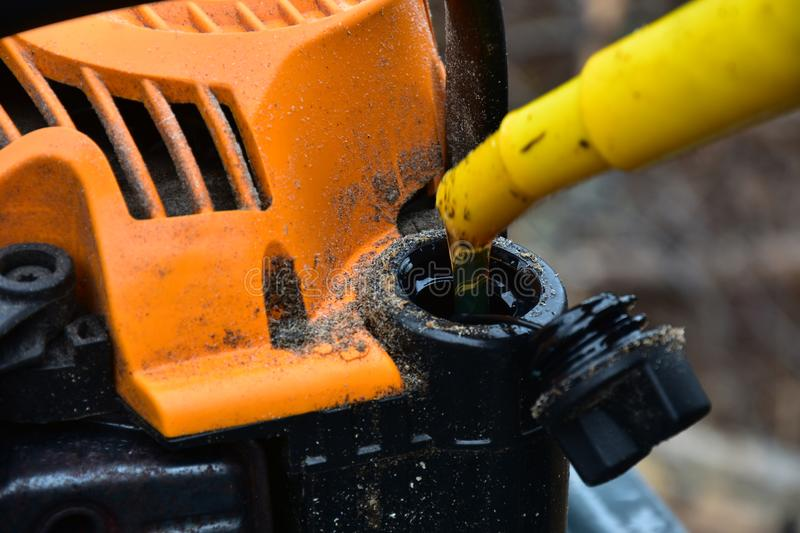 Chainsaw and Mix Oil. A close up image of an old dirty chainsaw with mix oil being added royalty free stock photo