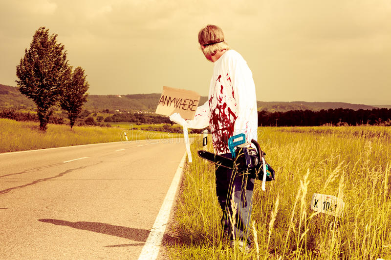Chainsaw Murderer Hitchhiking. Chainsaw murderer trying to get a ride. any destination is fine for him stock image