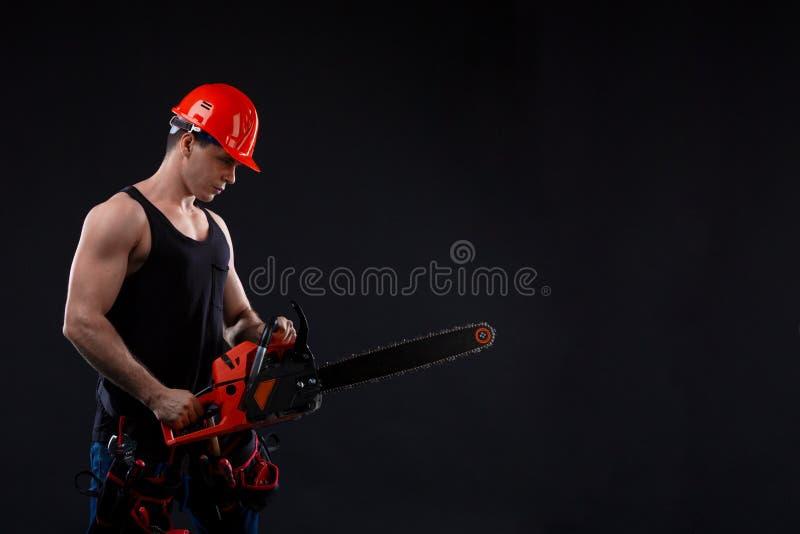Chainsaw och ung arbetare Den nakna mannen bröt chainsawen Attraktiv grabb med hjälpmedlet på svart bakgrund Byggmästare eller sk arkivbilder