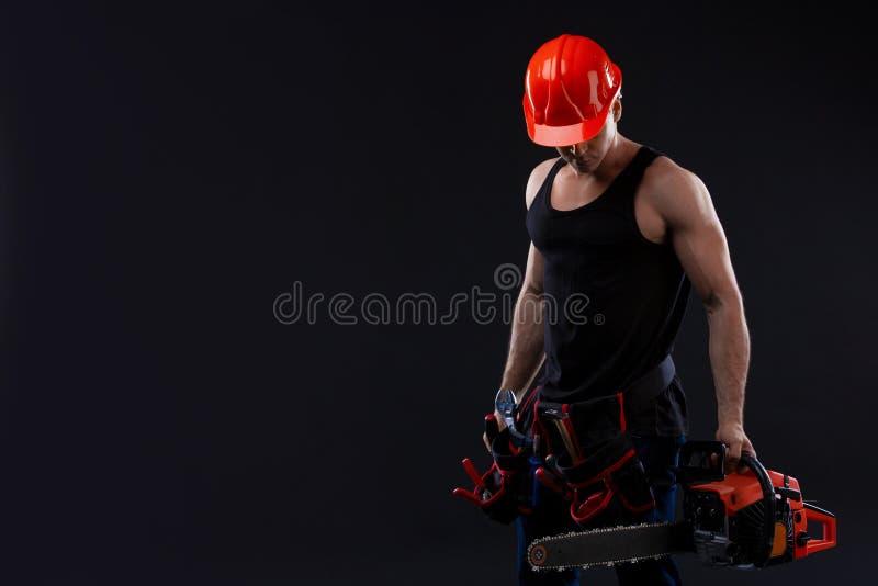 Chainsaw och ung arbetare Den nakna mannen bröt chainsawen Attraktiv grabb med hjälpmedlet på svart bakgrund Byggmästare eller sk arkivfoton