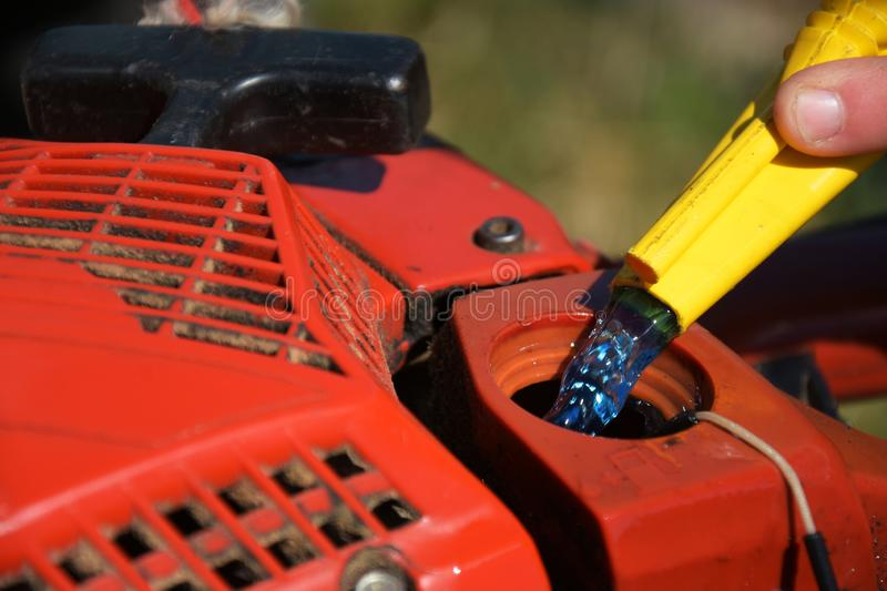 Chainsaw Refueling. A close up image of a old red chainsaw being refueled royalty free stock photos