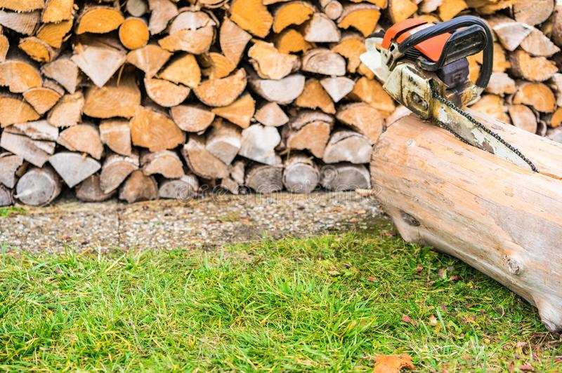 Chainsaw with tree trunk in front of a firewood stack. Prepairing chainsaw for cutting fire wood from trees stumps, copy space stock images