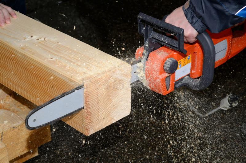 With a chainsaw, wood is cut. Large wooden beam is cut off with chainsaw - close-up stock photo