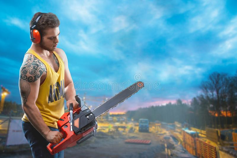 Chainsaw and young worker. The naked man broke the chainsaw. Attractive guy with tool on building background. Builder or lumberjac royalty free stock photo