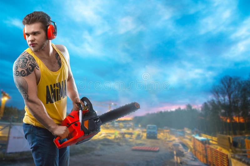 Chainsaw and young worker. The naked man broke the chainsaw. Attractive guy with tool on building background. Builder or lumberjac stock photos