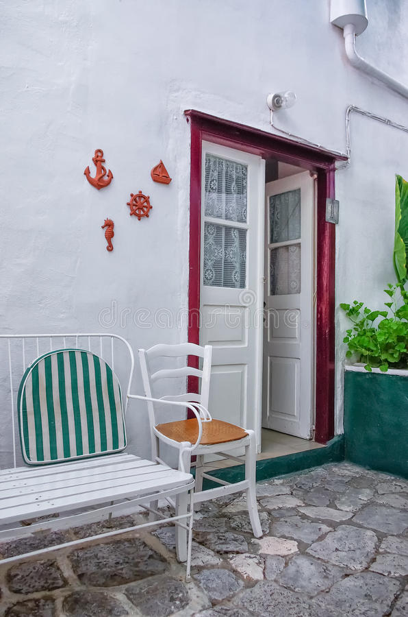 Chair in the alley. Yard of an old Greek house, in Hydra island stock images