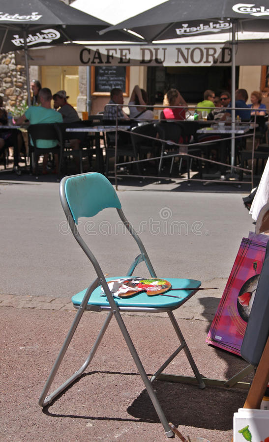Chair and artist`s pallet in a French market. With a cafe in the background royalty free stock photo
