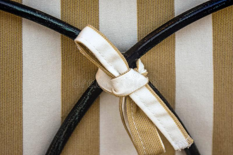Chair back decor element: textile bow on striped fabric background, tied to curved metal details. Close-up. Copy space stock photos