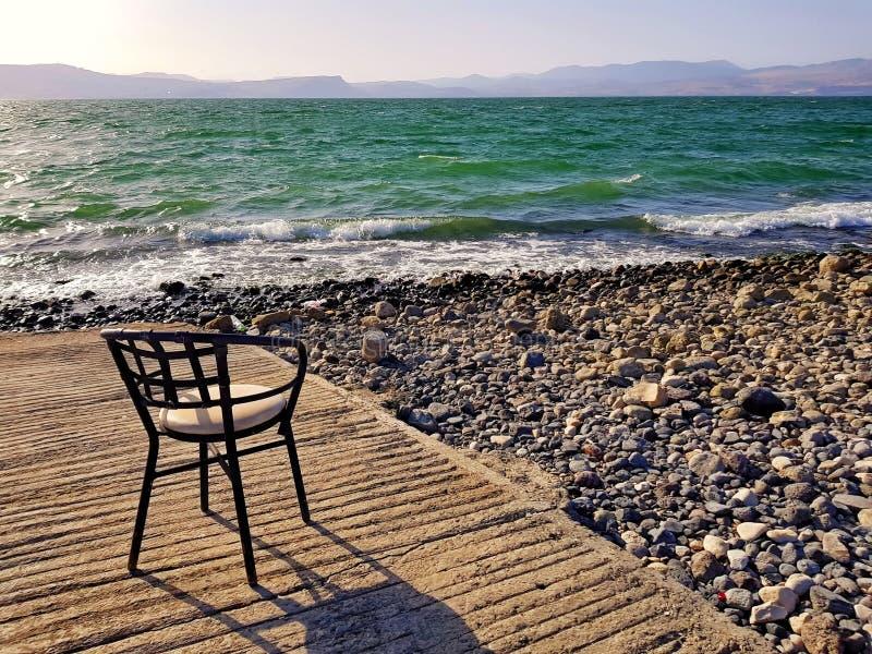 Chair on beach of Sea of Galilee lake stock image