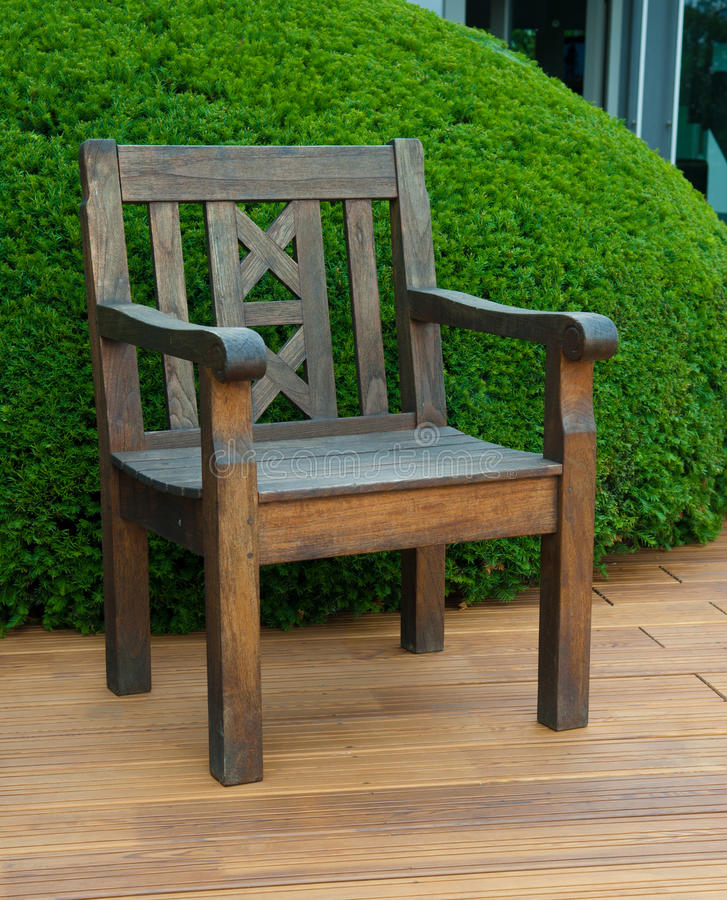 Chair on the deck. Chair on the wooden deck with a topyary yew royalty free stock photo