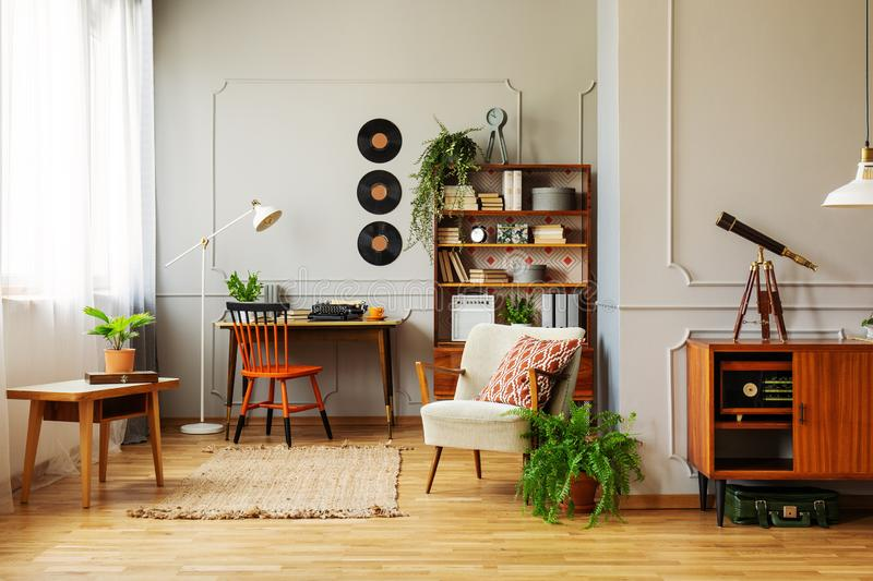 Chair at desk near armchair and wooden table in retro workspace interior with vinyl. Real photo stock image