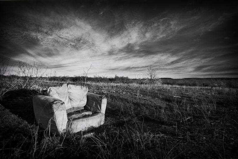 Chair in a field. Black and white image of a chair in a field around sunset on a cloudy day royalty free stock photo