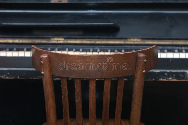 Chair in front of a retro piano stock photos
