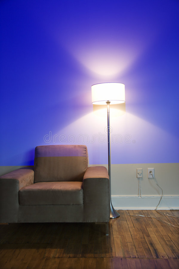 Chair and lamp with blue wall. royalty free stock images