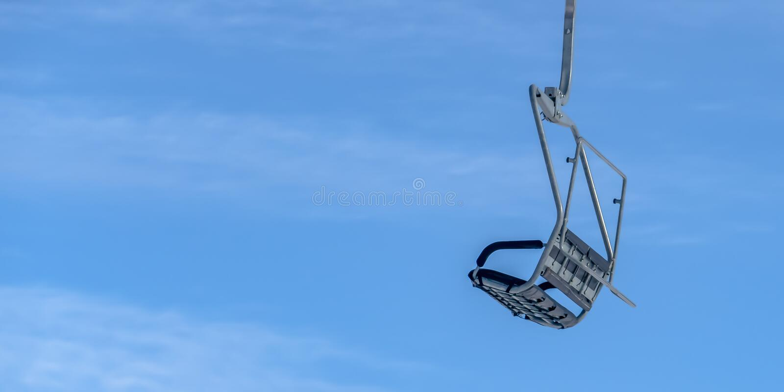 Chair lift against blue sky in Park City Utah. Close up view of an empty chair lift with bright blue sky in the background. Ski lift on a ski resort in Park stock image