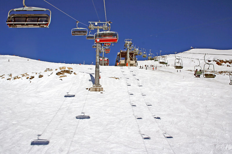 Chair lift in alps in full sun. Chair lift in alps in clear weather royalty free stock photo
