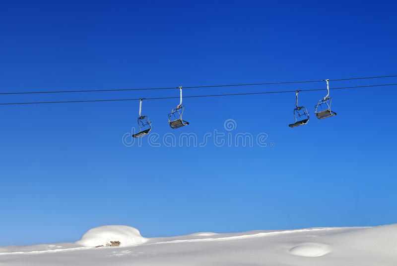Chair-lift and blue clear sky at sunny day. Greater Caucasus, Mount Shahdagh, Qusar rayon of Azerbaijan stock photography