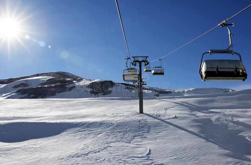 Chair-lift and blue sky with sun. Greater Caucasus, Mount Shahdagh. Qusar rayon of Azerbaijan royalty free stock images