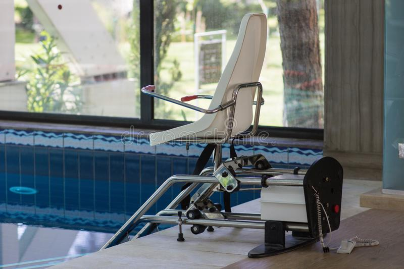 Chair lift device for disabled people in close swimming pool stock images