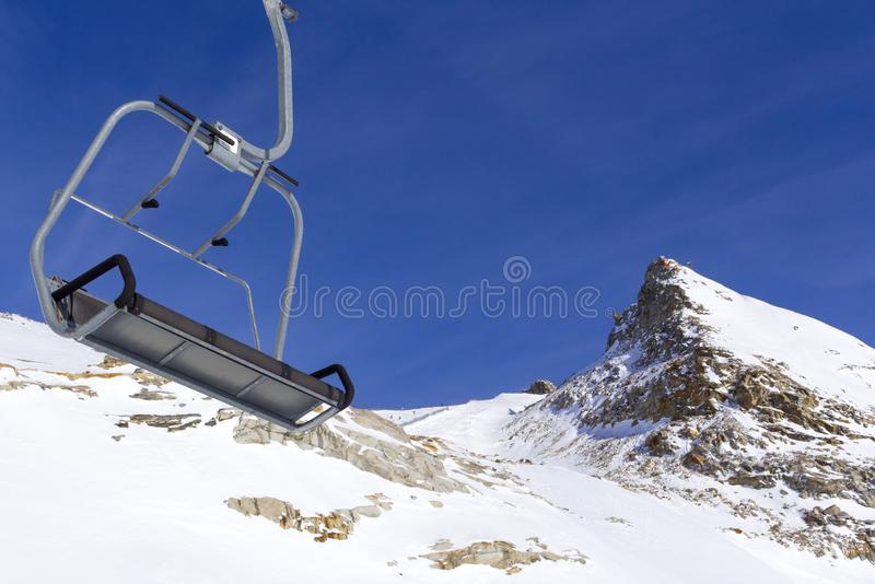 Chair lift in the foreground against the background of snow-capped mountains and blue sky.Austrian Alps in winter stock photography