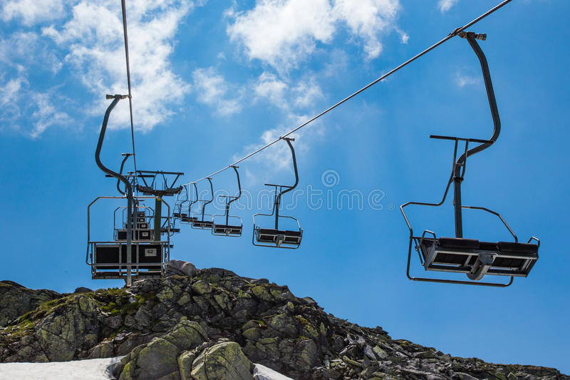 Chair lift in the mountains. Modern chair lift in the high mountains stock images