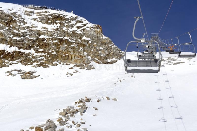 Chair lift move up and cableway in the foreground against the background of snow-capped mountains and blue sky.Austrian Alps in stock images