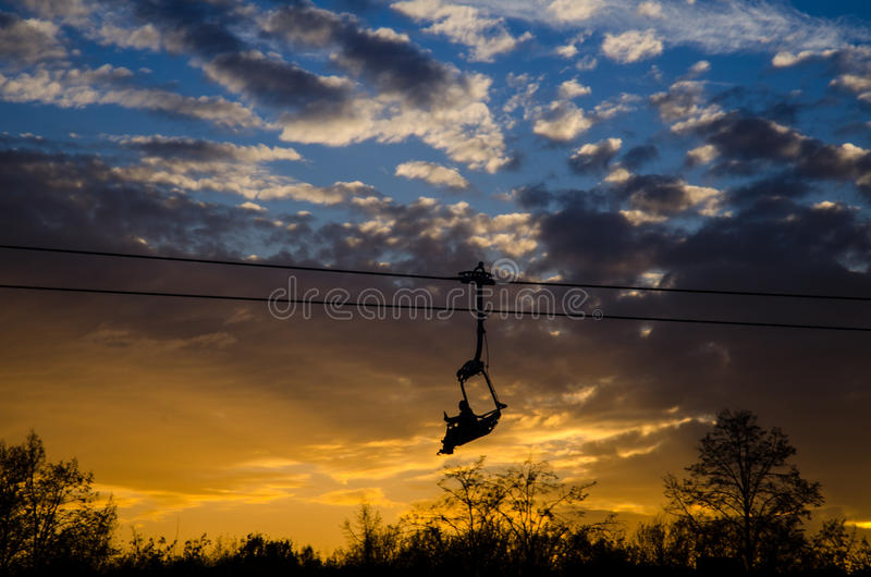 Chair lift in Silesia Park. In Chorzow, Poland. This photo was taken as the sun was setting behind the trees in the background royalty free stock photos