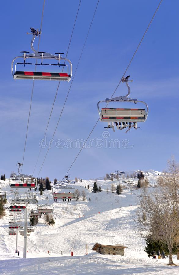 Chair lift under blue sky and above ski slope. In french alps stock photo