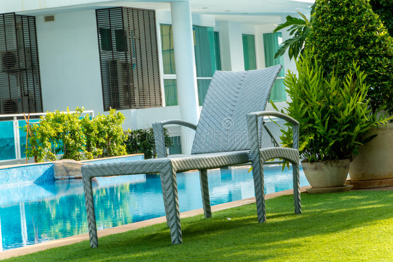 Chair near swimming pool. In home stock photography