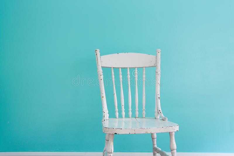Chair. Old white chair in front of a wall. Natural light from the window stock image