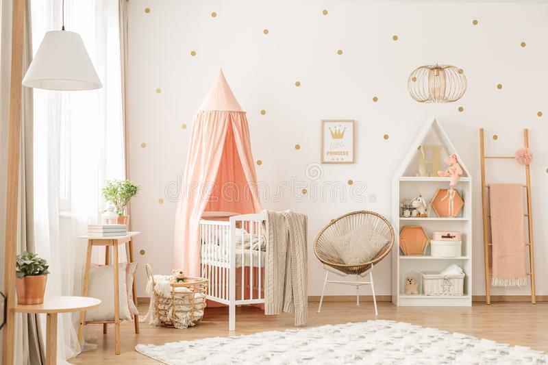 Chair with pillow. Gold chair with pillow standing next to a white wooden crib with pastel pink canopy in bright baby room interior with dots on the wall royalty free stock image
