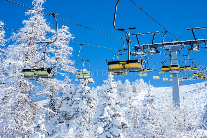 Chair ski lift. On background of sky and winter forest royalty free stock photos