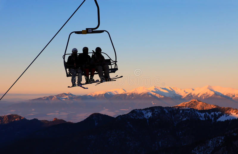 Chair ski lift with skiers. Over blue sky and mountains royalty free stock image