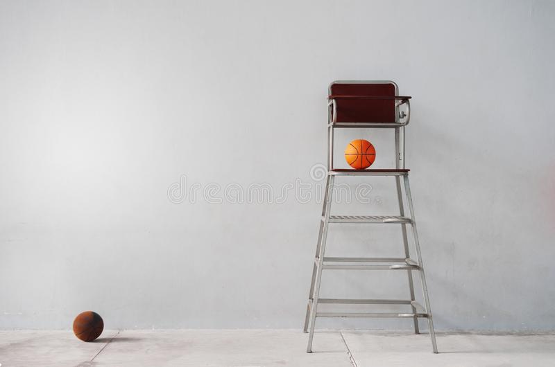 Chair of sport referee with orange basketball in gymnasium gray royalty free stock photo