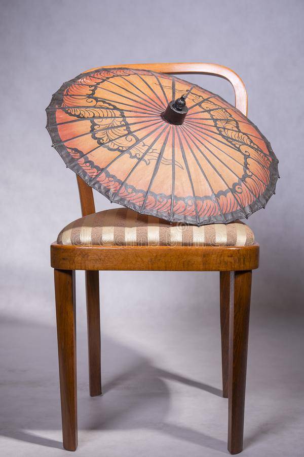 Chair and umbrella. Retro chair with stripes sit and paper chinese umbrella, isolated royalty free stock images