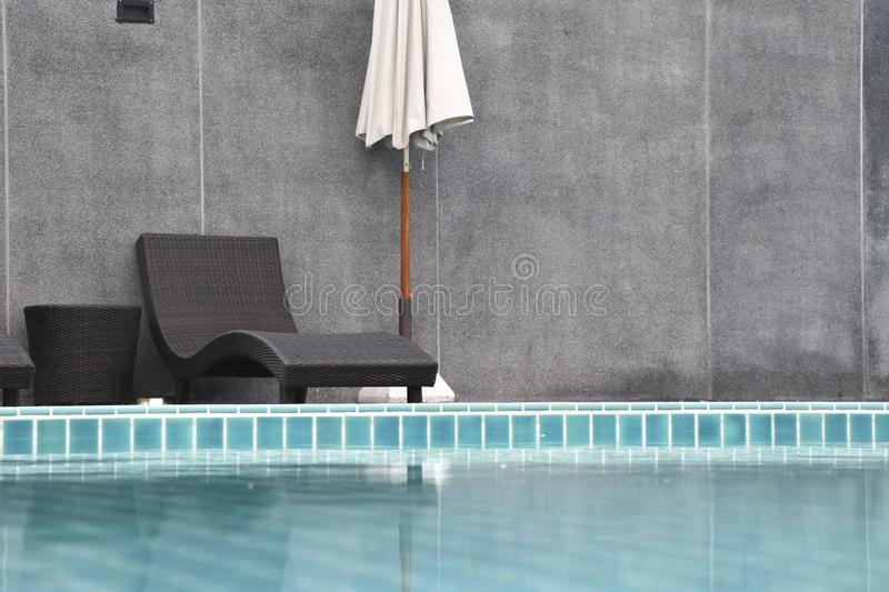Chair and umbrella set beside the swimming pool. Swimming pool and surface of water stock photo