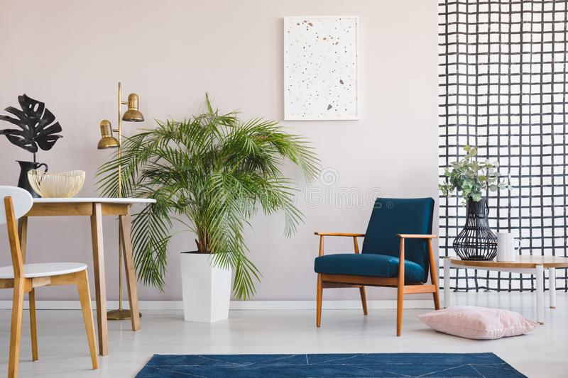 Chair at wooden table in bright dining room interior with plants and poster above armchair. Real photo stock illustration