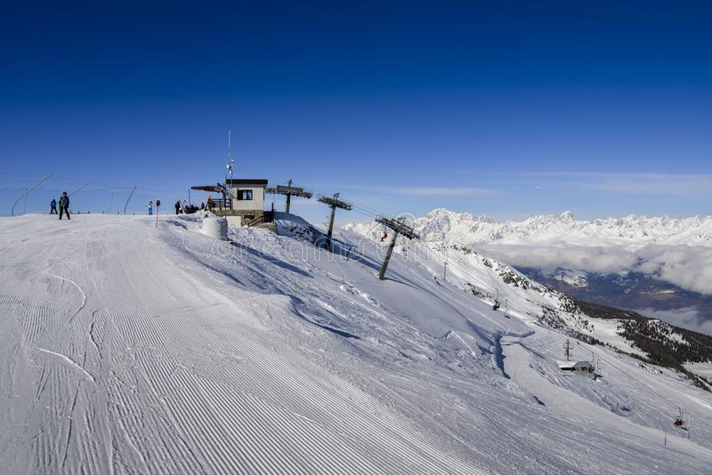 Chairlift at Italian ski area of Pila on snow covered Alps and pine trees during the winter with Mt. Blanc in France visible in ba royalty free stock photo