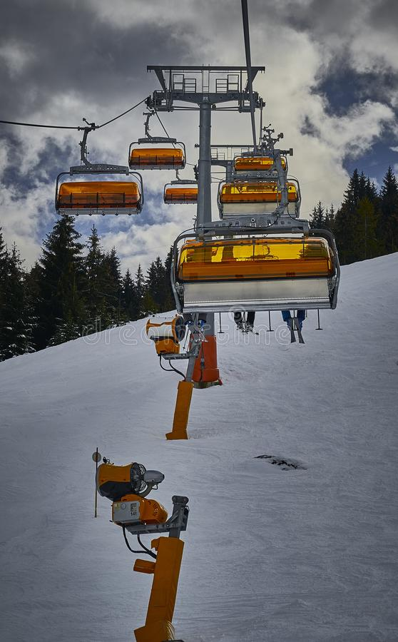 A chairlift to the top of the mountain. A chairlift to take you to the top of the mountain, snow making devices are also visible stock image
