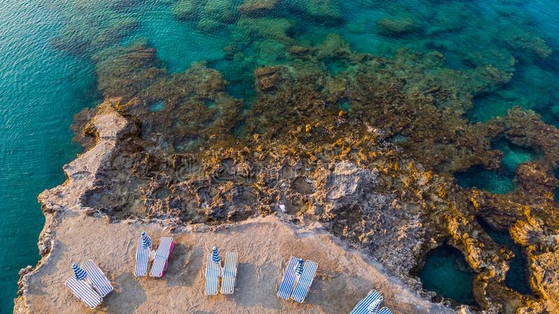 Chairs on Beach by Turquoise Water on Greek Island, Drone View royalty free stock photo