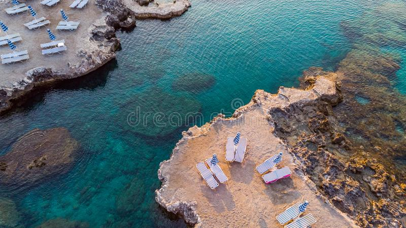Chairs on Beach by Turquoise Water on Greek Island, Drone View royalty free stock image