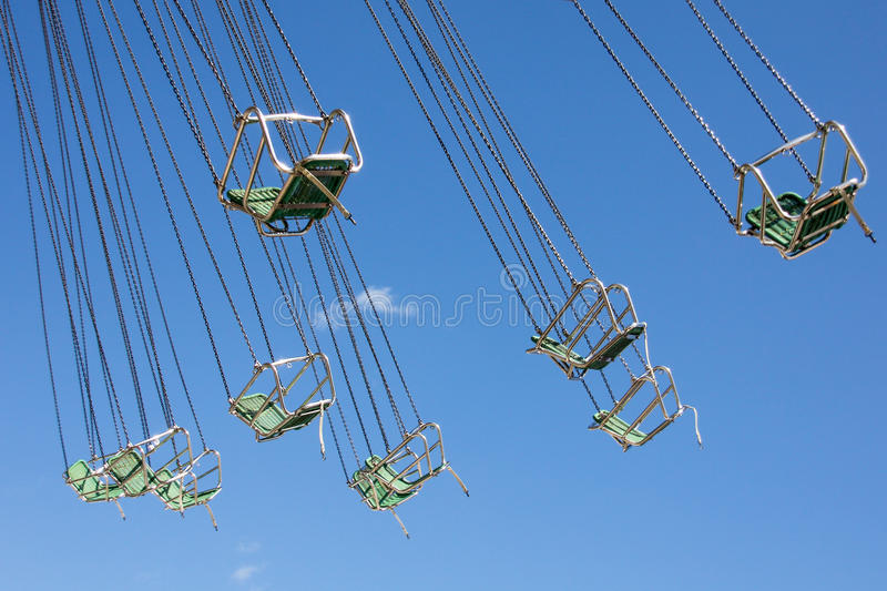 Carousel in motion. Chairs of classic carousel in motion, without people. Blue sky royalty free stock photos