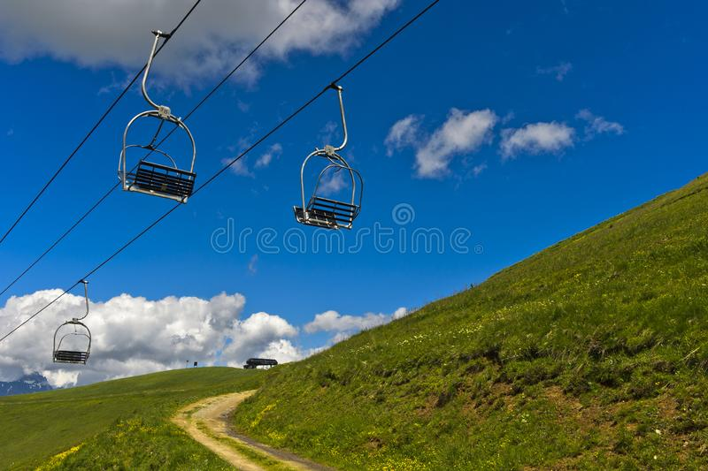 Chairs of a chairlift dangle over a hiking trail royalty free stock photo